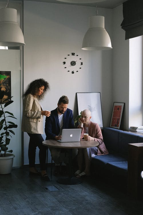 Diverse coworkers using laptop and speaking about job