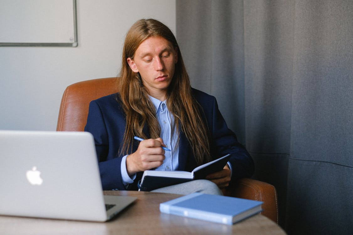 Pensive androgynous businessman in formal suit sitting at table with laptop and book and taking notes in notebook in workspace