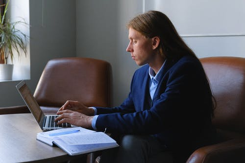 Side view of pensive androgynous entrepreneur with long hair in formal suit sitting at table with notebook and working on project on laptop in workspace in daytime