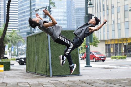 Young ethnic male athletes doing backflip on street