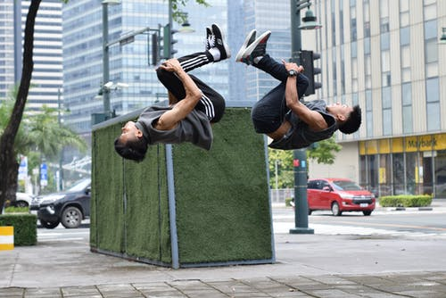 Side view of determined young Asian male athletes in sportswear doing backflip while training together on city street