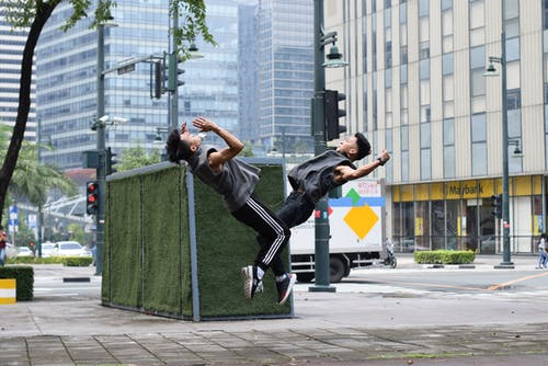 Young Asian male athletes jumping on street during workout on street