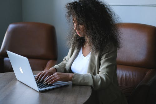 Side view of young ethnic female in stylish outfit browsing laptop while sitting at table and working on project in office