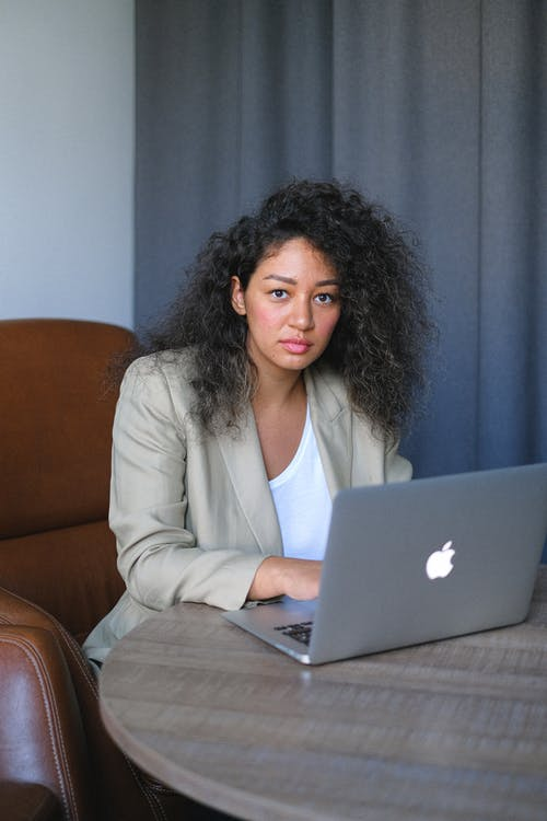 Concentrated woman with curly hair wearing formal clothes sitting at table in office and browsing netbook