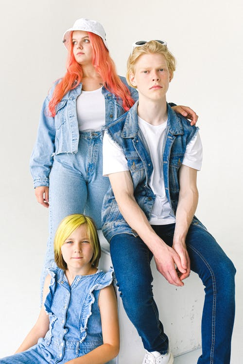 Group of models wearing casual clothing and denim jackets in studio against white background