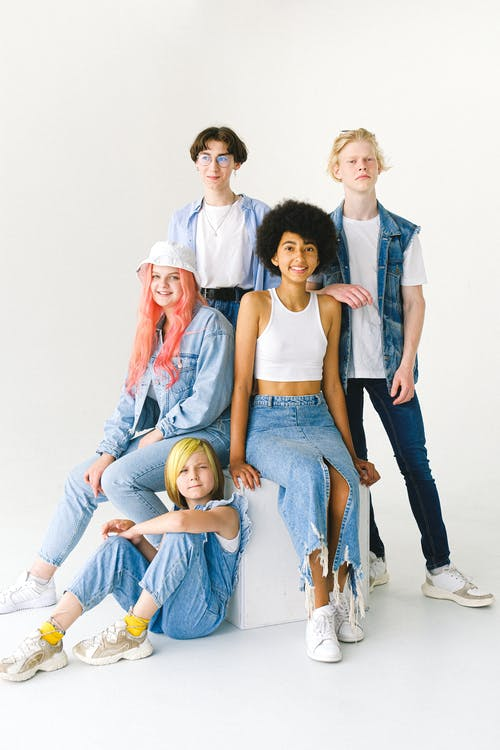Smiling diverse female models and teen males in denim clothes