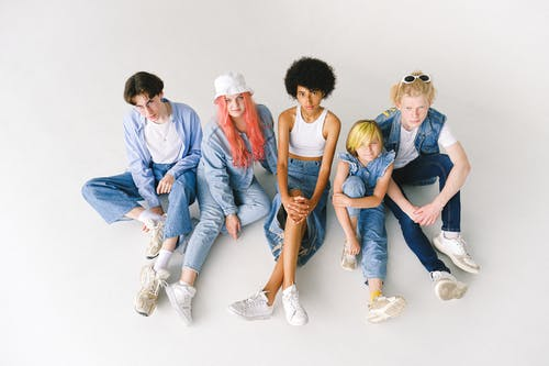 From above full body of diverse models wearing stylish denim outfits sitting on white floor in studio