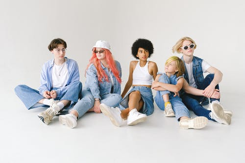 Full body of serious multiracial teens and small girl wearing denim outfits sitting on floor against white wall