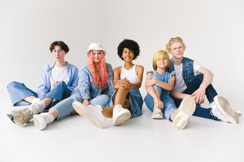 Full body of positive multiethnic models in denim casual clothes sitting on floor and smiling to camera