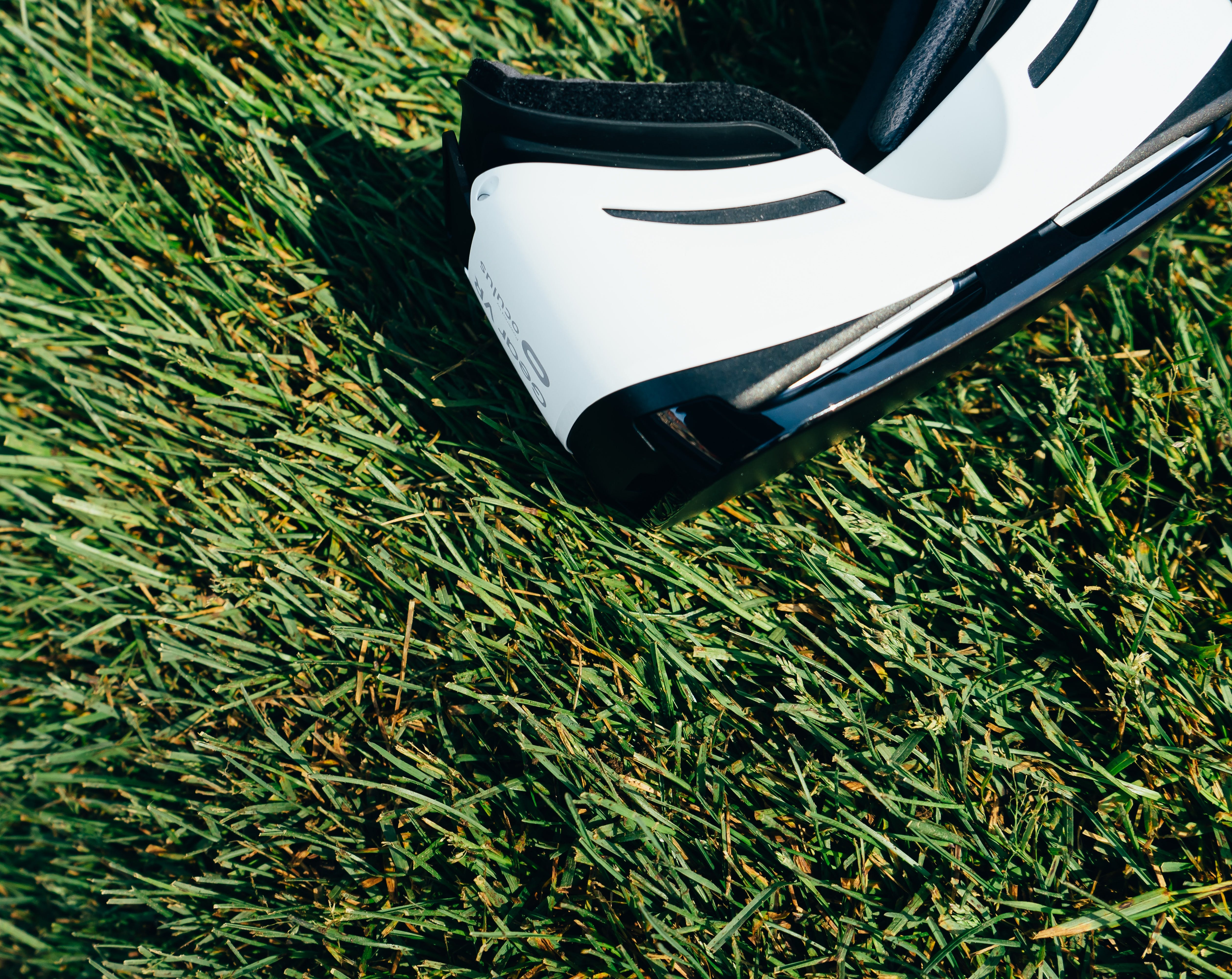 White and Black Vr Headset on Green Grass