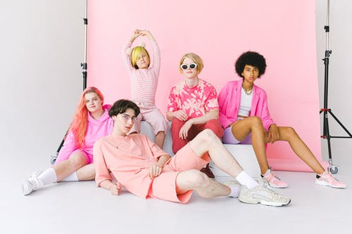 Full length calm informal diverse teenage friends in pink outfits sitting near pink backdrop and looking at camera