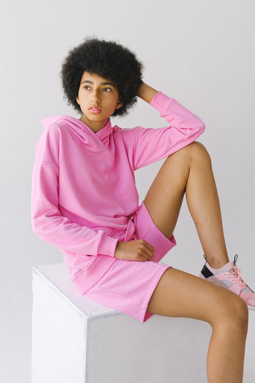 Contemplative young African American female in pink outfit with afro hairstyle looking away touching head on white background
