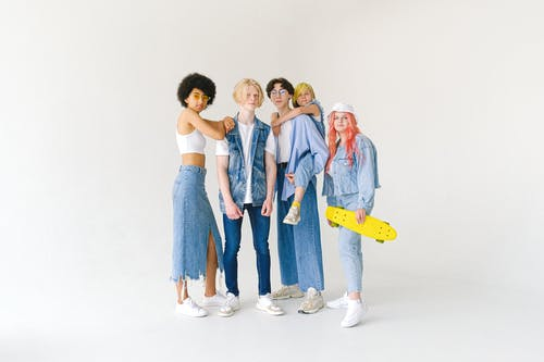 Full body group of teenager friends in jeans wear and glasses with yellow penny board on white background looking at camera