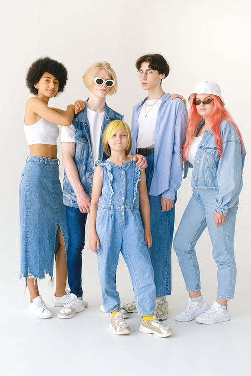 Full body group of teenager friends in stylish denim clothes on white background looking at camera