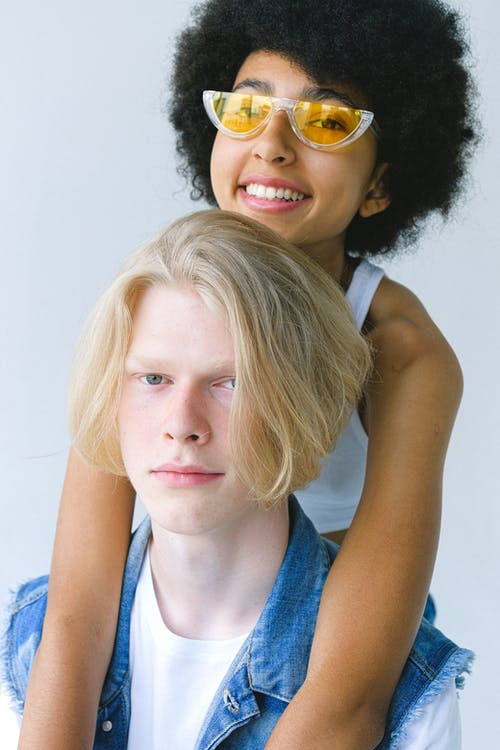 Cheerful loving multiracial couple doing piggyback riding on white background and looking at camera
