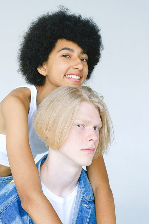 Delighted young multiracial couple looking at camera while doing piggyback riding on white background