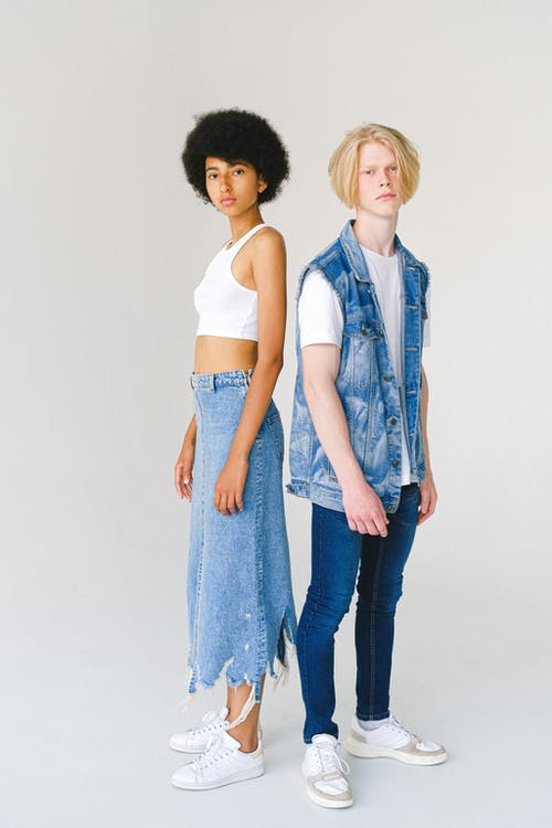 Full body serious multiracial young couple standing against white background and looking at camera