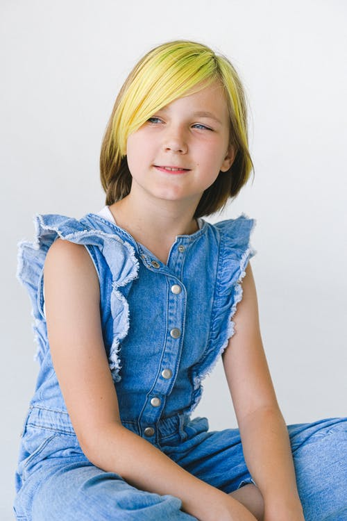 Cheerful girl with dyed hair in sleeveless denim overall on white background looking away