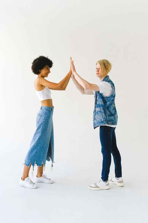Side view full body cheerful diverse young couple in jeans clothes touching hands while giving high five on white background