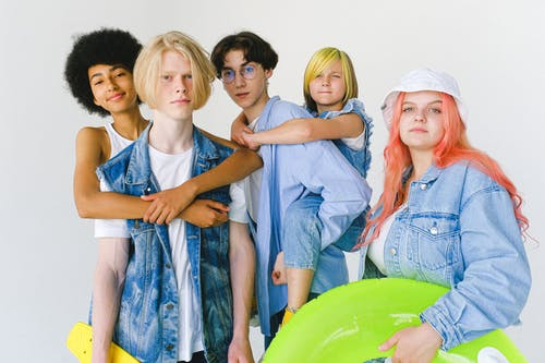 Cool multiethnic teenagers and schoolchild in casual denim outfit standing in studio with inflatable ring and skateboard and giving piggyback and hugging while looking at camera on white background