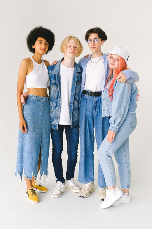 Full body of multiethnic teenagers in casual denim outfit standing in studio and hugging on white background while looking at camera