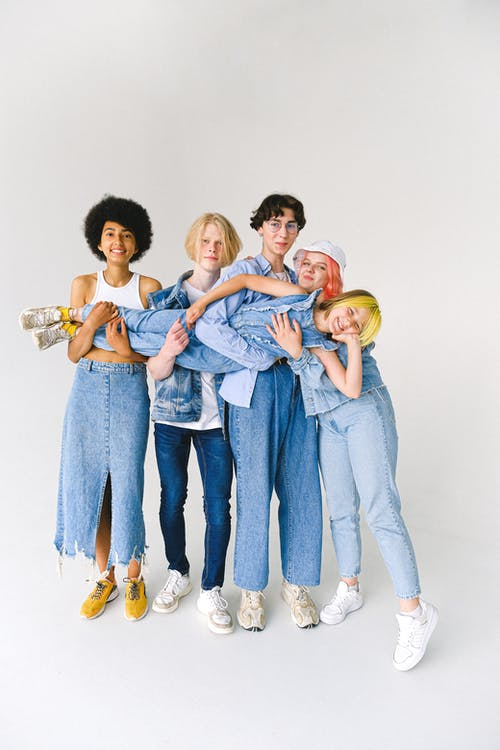 Full length of multiracial friends in casual clothes standing in studio while holding child on hands on white background while looking at camera