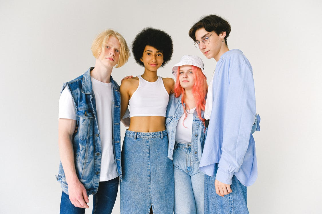 Content diverse teenager friends wearing denim clothes standing against white background hugging and looking at camera