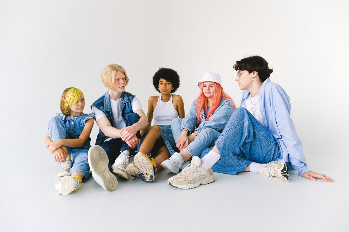 Full body group of thoughtful multiethnic teenager friends in jeans clothes sitting on floor and speaking with each other against white background