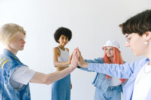 Content teenager friends in denim clothes standing together against white background with hands stacked
