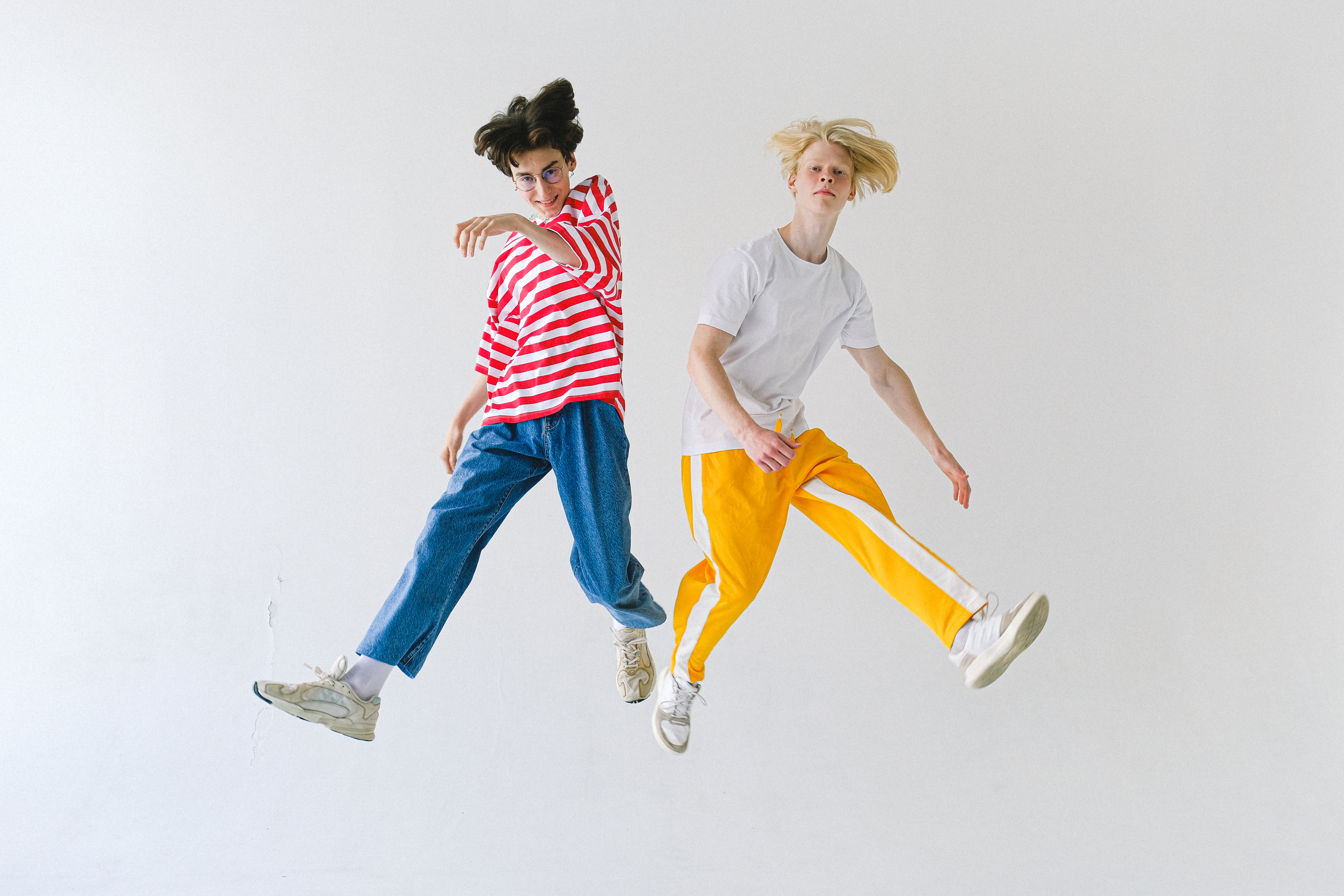 cheerful friends jumping above floor and looking at camera