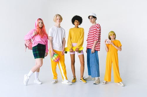 Full body group of informal teenager friends in colorful outfits standing against white background with ball and penny board with photo camera and backpack looking at camera