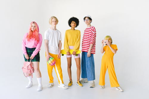 Full length group of multiracial teenager friends in bright colorful outfits standing against white wall with photo camera and ball with backpack and penny board looking at camera