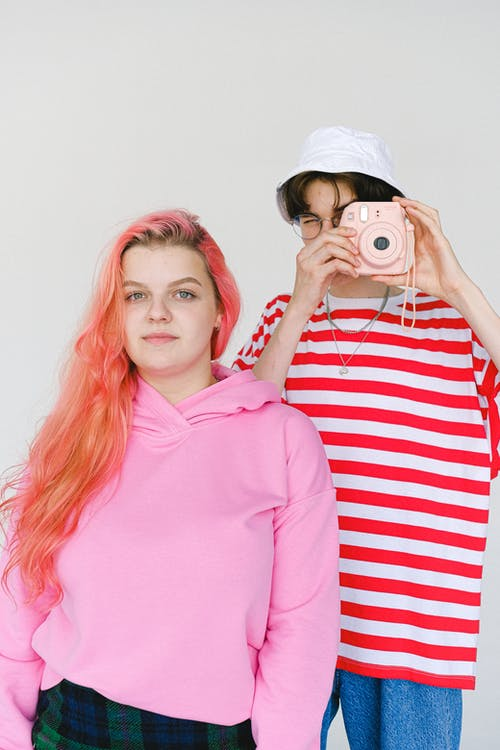 Calm informal teenager couple wearing bright colorful outfits taking picture on modern instant photo camera and looking at camera standing against white wall