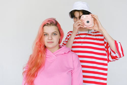 Calm informal teenager couple in bright colorful clothes standing against white background and taking picture on modern instant photo camera