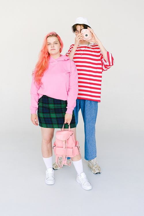 Full body calm informal couple of teenagers in vivid colorful outfits with modern photo camera and backpack against white wall looking at camera