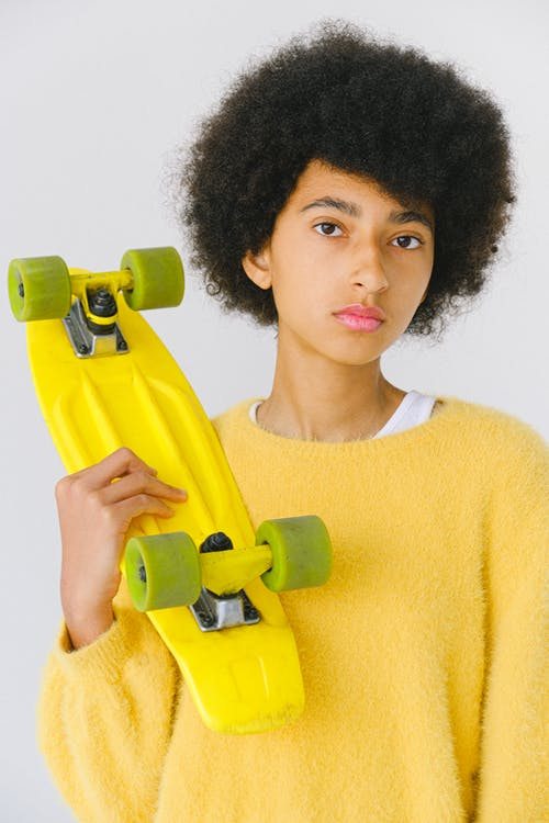 Calm informal teenage African American female skater with yellow penny board on white background looking at camera