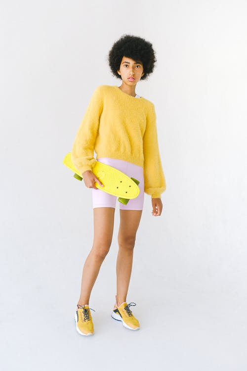 Full body serious teenage African American female skater in colorful outfit with yellow penny board standing against white background and looking at camera