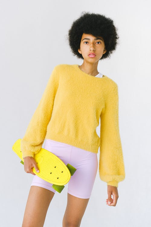 Serious teenage African American female skater in vivid yellow sweater with penny board against white background looking at camera