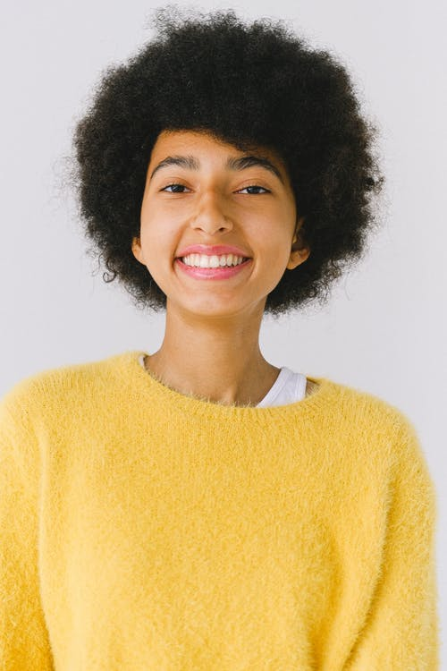 Happy young African American female in vivid yellow sweater against white background looking at camera smiling