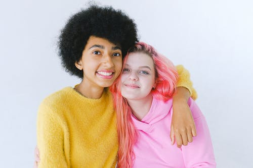 Happy multiethnic teen girlfriends in trendy colorful outfit smiling and looking at camera on white background