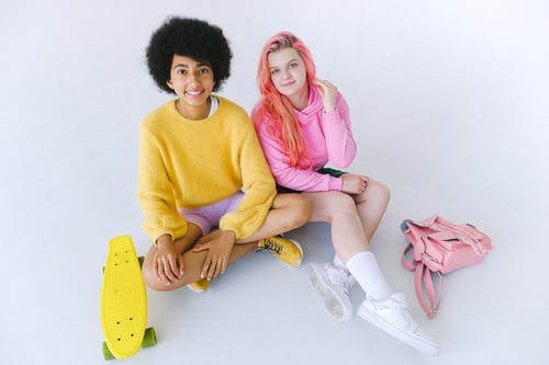 Delighted multiethnic teenage girls with skateboard and stylish backpack
