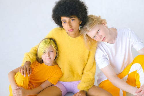Diverse teenage friends with unusual hairstyles looking at camera on white background of studio