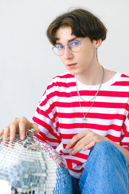 Teenage boy in striped T shirt with disco ball