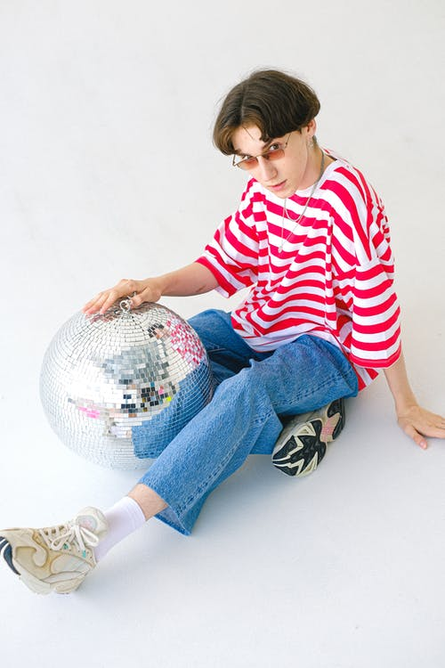 Teenager in trendy casual outfit with sparkling disco ball
