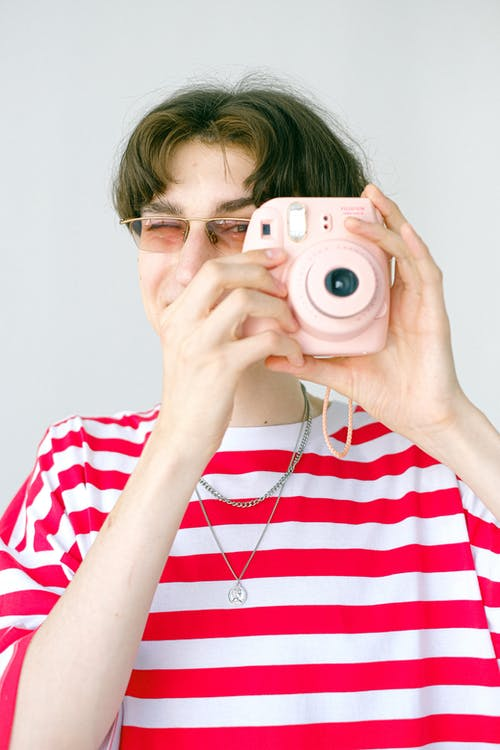 Teenagers in bright red and white striped T shirt and eyeglasses taking photo with instant camera on white background