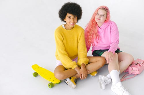Happy multiethnic stylish teenage friends with skateboard and backpack