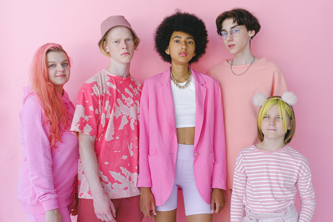 Group of multiracial teenage boys and girls looking at camera on pink background of studio