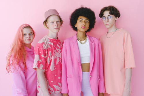 Diverse teenage friends in trendy outfits looking at camera on pink background of studio