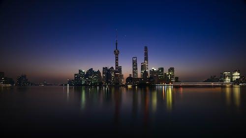 akşam, aydınlatılmış, binalar, deniz kenarı içeren Ücretsiz stok fotoğraf