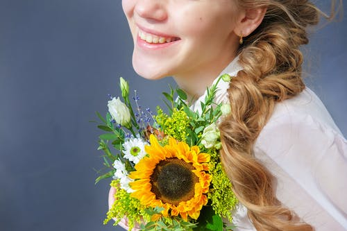 Crop happy young female with braid standing with delicate sunflower bouquet against gray wall in studio